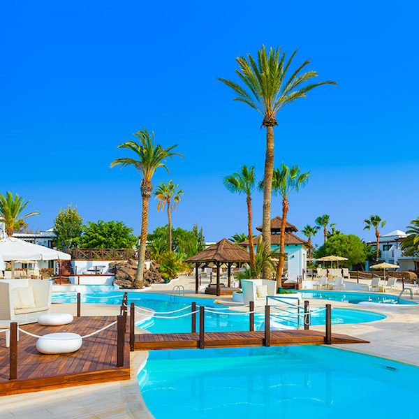 Pools and palm trees at H10 Sentido White Suites Hotel